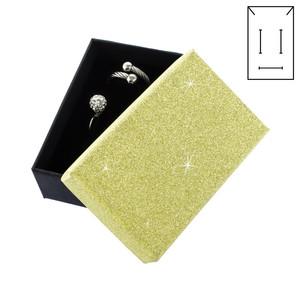 Černá krabička s žlutým třpytivým víčkem a černým polstrováním