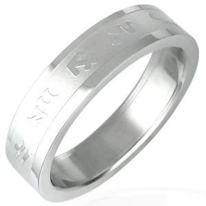 Ocelový prsten s hrubě broušeným středem a lesklými symboly